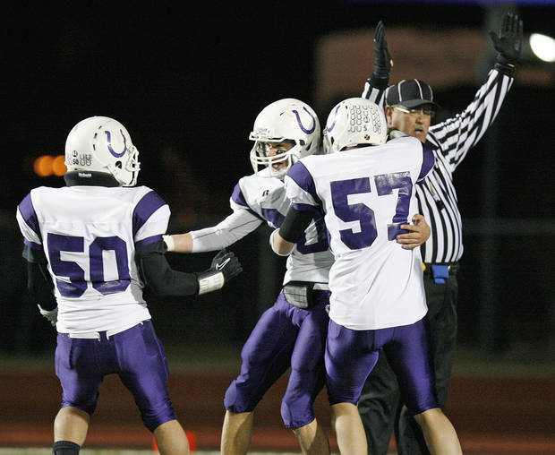 Bethany's Gage Diffee (20), middle, celebrates with teammates Michael Paul (50) and Brett Gilstrap (57) after Diffee scored in the first quarter during the Class 3A high school football semifinal playoff  game between Heritage Hall and Bethany at Putnam City High School in Oklahoma City, Saturday, December 4, 2010. Photo by Nate Billings, The Oklahoman