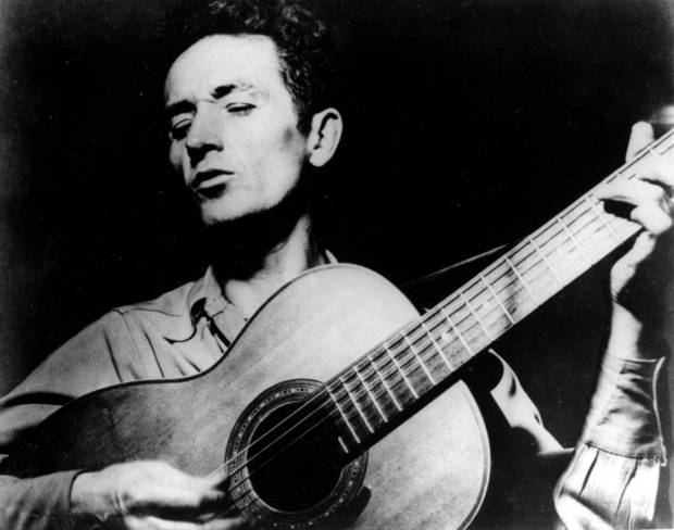 "FILE - This undated file photo shows folk singer Woody Guthrie playing his guitar and singing. Guthrie's writings, recordings and artwork will land in his native state after an Oklahoma foundation bought the collection, with plans for a display that concentrates on his artistry rather than the populist politics that divided local opinion over the years. Guthrie, known for the anthem, ""This Land is Your Land"" and his songs about the poor and downtrodden, is remembered mostly as a musician, composer and singer, but was also a literary figure and an artist, said Bob Blackburn, executive director of the Oklahoma Historical Society.   (AP Photo/File) ORG XMIT: CER102"