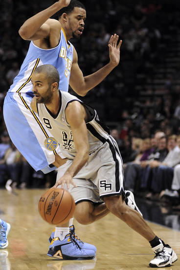 San Antonio Spurs' Tony Parker (9), of France, drives past Denver Nuggets' JaVale McGee during the first half of an NBA basketball game, Saturday, Nov. 17, 2012, in San Antonio. (AP Photo/Darren Abate)