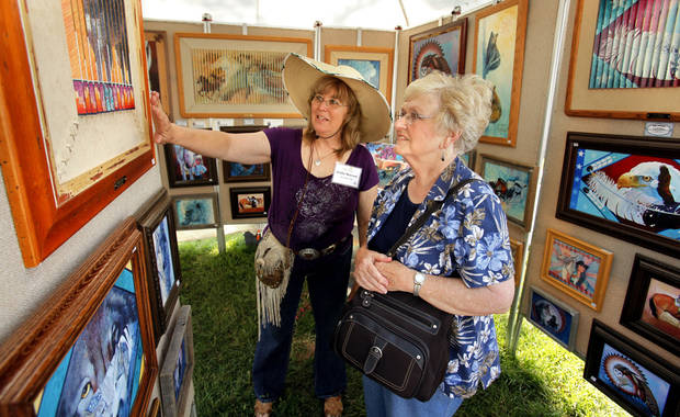 Artist Kathy Morrow shows her work to Louise Lazalier at the annual May Fair Festival Saturday at Andrews Park in Norman. PHOTO BY STEVE SISNEY, THE OKLAHOMAN <strong>STEVE SISNEY</strong>