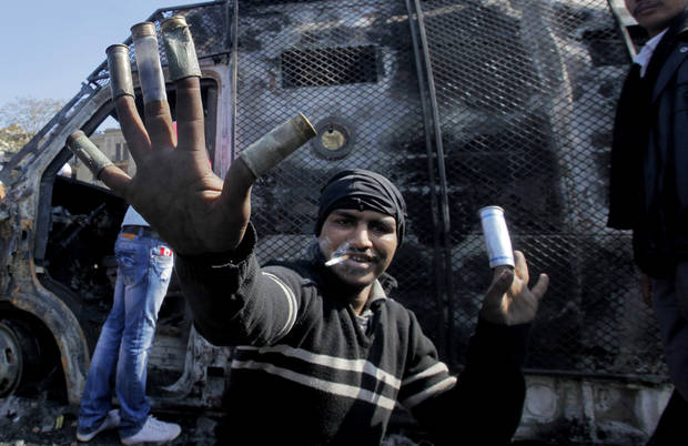 An Egyptian protester displays used ordinance as others, not pictured, celebrate the capture of a state security armored vehicle that demonstrators commandeered during clashes with security forces and brought to Tahrir Square in Cairo, Egypt, Tuesday, Jan. 29, 2013. Egypt�s army chief warned Tuesday of the �the collapse of the state� if the political crisis roiling the nation for nearly a week continues, but said the armed forces will respect the right of Egyptians to protest. (AP Photo/Amr Nabil)
