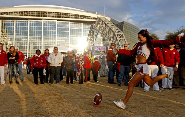 A member of the OU Cheer Squad kicks a football outside Cowboys Stadium before the Cotton Bowl college football game between the University of Oklahoma (OU)and Texas A&M University at Cowboys Stadium in Arlington, Texas, Friday, Jan. 4, 2013. Photo by Bryan Terry, The Oklahoman