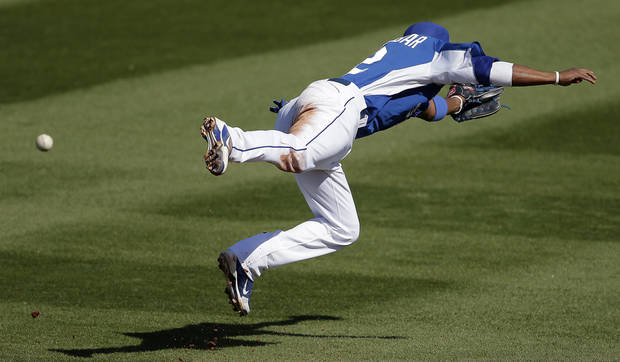 Kansas City Royals shortstop Alcides Escobar dives for but misses a single hit by Cincinnati Reds' Donald Lutz during the fourth inning of an exhibition spring training baseball game on Friday, March 1, 2013, in Surprise, Ariz. (AP Photo/Charlie Riedel)
