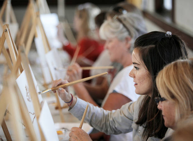 Alyse Cox and other participants paint during the Performing Art Studio�s �Corkscrews and Canvas� painting party Thursday at the Santa Fe Depot in Norman. PHOTOS BY NATE BILLINGS, THE OKLAHOMAN