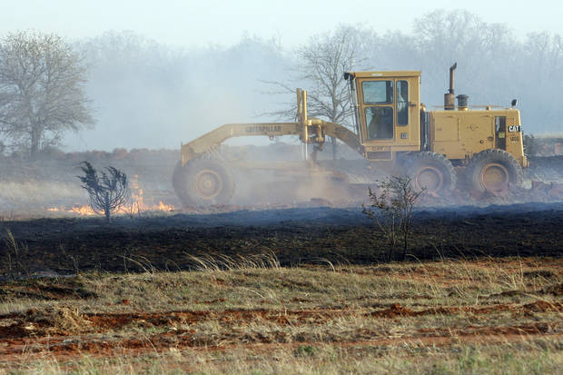 A grader driver tries to stop wildfires which destroyed 12 structures in Lindsay, Okla., on Thursday, April 9, 2009.  Photo by Steve Sisney, The Oklahoman