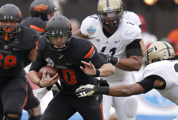 Oklahoma State's Clint Chelf (10) runs past Purdue's Max Charlot (34) during the Heart of Dallas Bowl football game between Oklahoma State University and Purdue University at the Cotton Bowl in Dallas, Tuesday, Jan. 1, 2013. Oklahoma State won 58-14. Photo by Bryan Terry, The Oklahoman