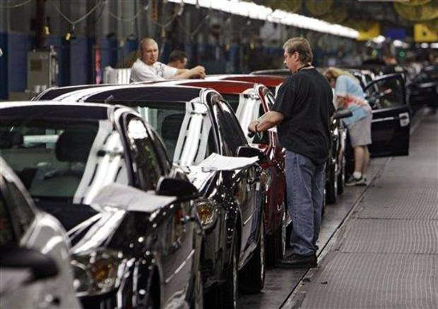 Workers at General Motors' Lordstown Assembly plant in Lordstown, Ohio put the final touches on Chevy Cobalts Tuesday, June 15, 2010. (AP Photo/Mark Duncan)