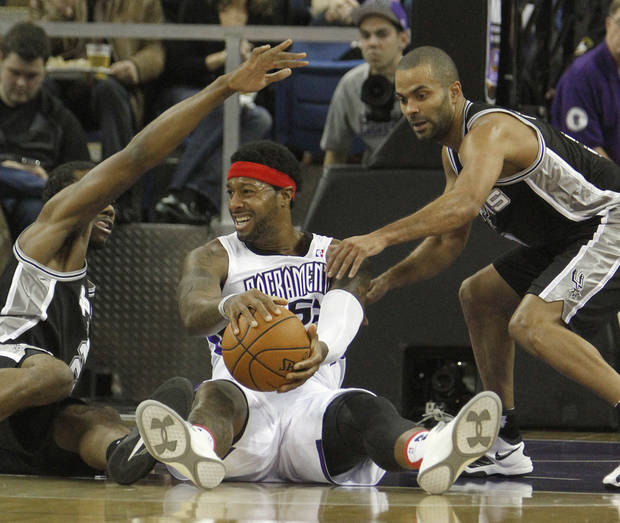 Sacramento Kings forward James Johnson, center, tries to protect the ball from San Antonio Spurs forward Kawhi Leonard, left, and Tony Parker during the first quarter of an NBA basketball game in Sacramento, Calif., Friday, Nov. 9, 2012. (AP Photo/Rich Pedroncelli)