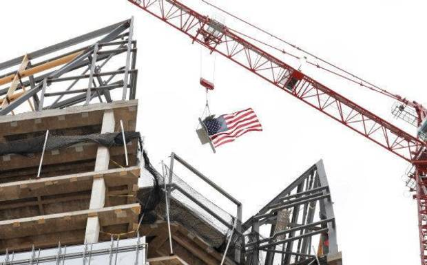 An evergreen tree and American flag attached to a beam are raised to the top of the tower under construction at the Devon Energy Center during a toping-out ceremony in downtown Oklahoma City Wednesday, Sept. 21, 2011. Photo by Paul B. Southerland, The Oklahoman ORG XMIT: KOD