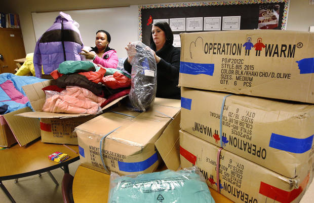 Erika Walker, left, and Jennifer Rader unpack boxes of new coats for students Monday at Southern Hills Elementary. Photo by Jim Beckel, The Oklahoman