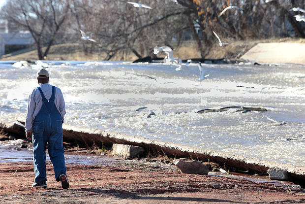 A fisherman walks Monday next to the water flowing into Lake Hefner from Canton Lake. Photo By David McDaniel, The Oklahoman
