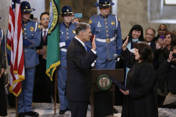 Jay Inslee, left, is sworn in as Washington state Governor, Wednesday, Jan. 16, 2013, by Washington Supreme Court Chief Justice Barbara Madsen,right, in the rotunda of the Legislative Building at the Capitol in Olympia, Wash. (AP Photo/Ted S. Warren)