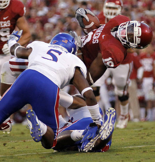 OU's Justin Brown (19) stretches for more yards past KU's Greg Brown (5) during the college football game between the University of Oklahoma Sooners (OU) and the University of Kansas Jayhawks (KU) at Gaylord Family-Oklahoma Memorial Stadium on Saturday, Oct. 20th, 2012, in Norman, Okla. Photo by Chris Landsberger, The Oklahoman