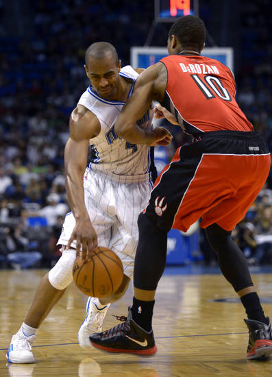 Orlando Magic forward Arron Afflalo, left, is fouled by Toronto Raptors guard DeMar DeRozan (10) while driving to the basket during the first half of an NBA basketball game in Orlando, Fla., Saturday, Dec. 29, 2012. (AP Photo/Phelan M. Ebenhack)
