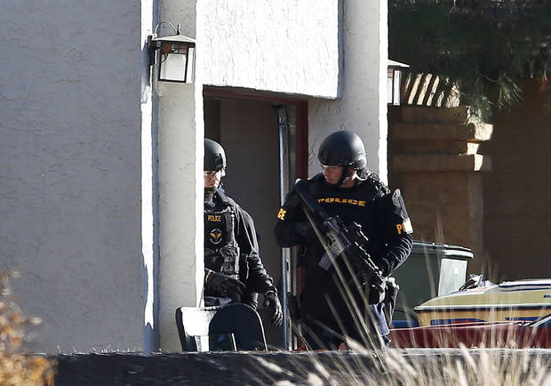 Members of the Phoenix Police Department SWAT team exit the garage at the home of a suspected gunman who opened fire at a Phoenix office building, wounding three people, one of them critically, and setting off a manhunt that led police to surround his house for several hours before they discovered he wasn&#039;t there, Wednesday, Jan. 30, 2013, in Phoenix.  Authorities believe there was only one shooter, but have not identified him or a possible motive for the shooting. They don&#039;t believe the midmorning shooting at the complex was a random act. (AP Photo/Ross D. Franklin)