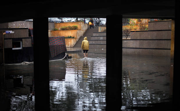 An Indian man wades past a waterlogged underpass as it rains in New Delhi, India, Tuesday, Feb. 5, 2013. Heavy rains accompanied by a thunderstorm lashed the capital for the second day Tuesday disrupting traffic across the city. (AP Photo/Altaf Qadri)