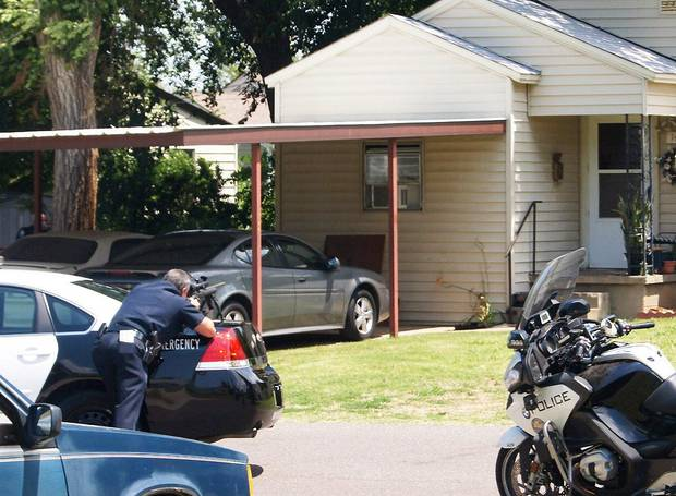 An officer aims his weapon  Friday at a house where a fatal shooting occurred in the 1400 block of Maple Drive in Midwest City.  Photo by  Bryan  Vanassche,  For The Oklahoman