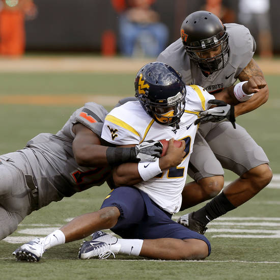 Oklahoma State's Shamiel Gary, at right,  and Shaun Lewis, bring down West Virginia's Geno Smith (12) during a college football game between Oklahoma State University (OSU) and West Virginia University at Boone Pickens Stadium in Stillwater, Okla., Saturday, Nov. 10, 2012. Oklahoma State won 55-34. Photo by Bryan Terry, The Oklahoman