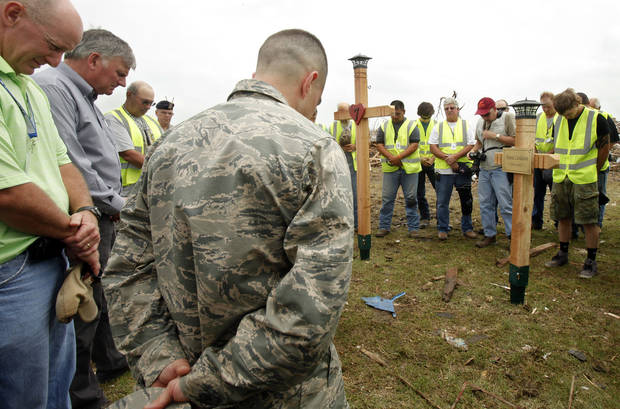 Franklin Graham, second from left, leads a prayer after workers installed crosses on Friday, May 24, 2013, outside of Plaza Towers Elementary for the seven victims killed at the school during the May 20 tornado in Moore, Okla. Photo by Aliki Dyer, The Oklahoman