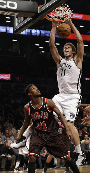 Brooklyn Nets center Brook Lopez, top, dunks over Chicago Bulls forward Jimmy Butler (21) in the first half of an NBA basketball game at the Barclays Center, Friday, Feb. 1, 2013,in New York. (AP Photo/Kathy Willens)