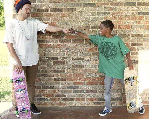 Matt Ramesh (left) celebrates with Moses Ward, age 11, of Edmond, after Ward landed a trick during a skate demonstration outside the Edmond Public Library in Edmond on Monday, July 12, 2010. Photo by John Clanton, The Oklahoman ORG XMIT: KOD