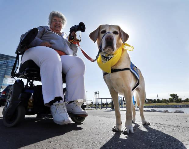 Dawn Ramsey, event coordinator, and her hearing assistance dog Penela, take part in DogFest Walk 'n' Roll Oklahoma City to benefit Canine Companions on Saturday. PHOTO BY STEVE SISNEY, THE OKLAHOMAN <strong>STEVE SISNEY - THE OKLAHOMAN</strong>