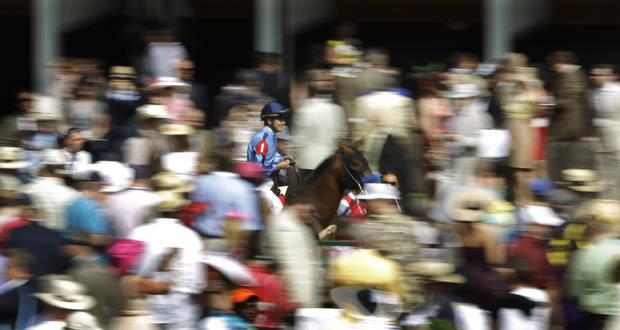 In a photo taken with a slow shutter speed, jockey Miguel Mena rides Rock N Glamour through the paddocks before the second race at the 138th Kentucky Derby horse race at Churchill Downs Saturday, May 5, 2012, in Louisville, Ky. (AP Photo/Matt Slocum)  ORG XMIT: DBY129