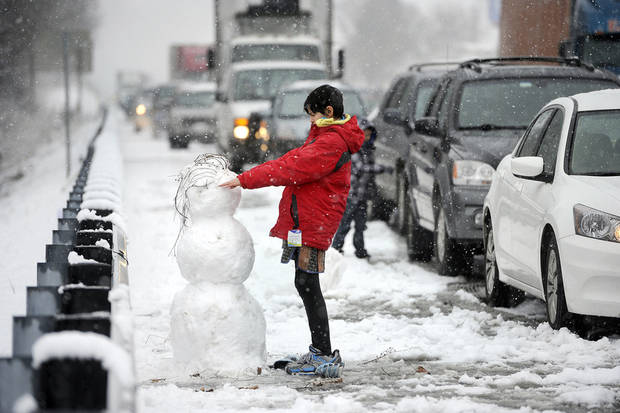Kristina Waymire, 13, of Baltimore, builds a snowman along the shoulder of Interstate 83 while waiting in stopped traffic for an hour and a half following a 14-vehicle wreck in York, Pa., on Saturday, Dec. 29, 2012. AP photo <strong>Jason Plotkin</strong>