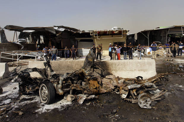Iraqis inspect the scene of a car bomb attack in the Ameen neighborhood of eastern Baghdad, Iraq, Sunday, Feb. 17, 2013. A series of car bombs exploded within minutes of each other as Iraqis were out shopping in and around Baghdad on Sunday, killing and wounding scores of people, police said. (AP Photo/ Khalid Mohammed)