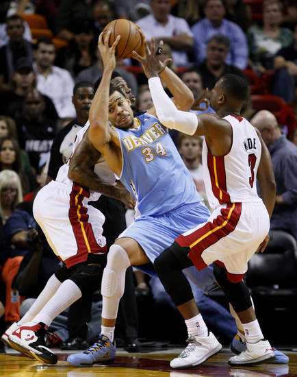 Denver Nuggets center JaVale McGee (34) finds himself in a tight spot between Miami Heat forward Udonis Haslem, rear, and guard Dwyane Wade, right, during the first half of an NBA basketball game, Saturday, Nov. 3, 2012 in Miami. (AP Photo/Wilfredo Lee)