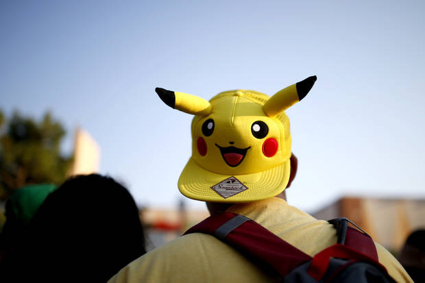 Anthony Acosta wears a Pikachu hat as he plays Pokemon Go during a meetup for players of the game in Oklahoma City at Bricktown on Friday, July 29, 2016. Photo by Bryan Terry, The Oklahoman