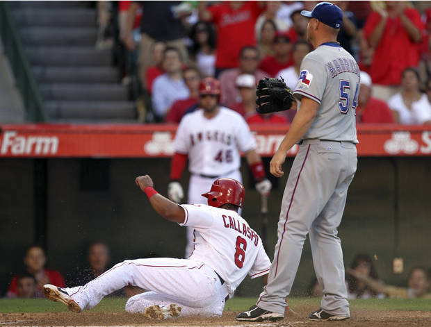 Los Angeles Angels' Alberto Callaspo scores on a passed ball by pitcher Matt Harrison, right, to catcher Yorvit Torrealba in the second inning of a baseball game in Anaheim, Calif., Sunday, July 22, 2012. (AP Photo/Reed Saxon)