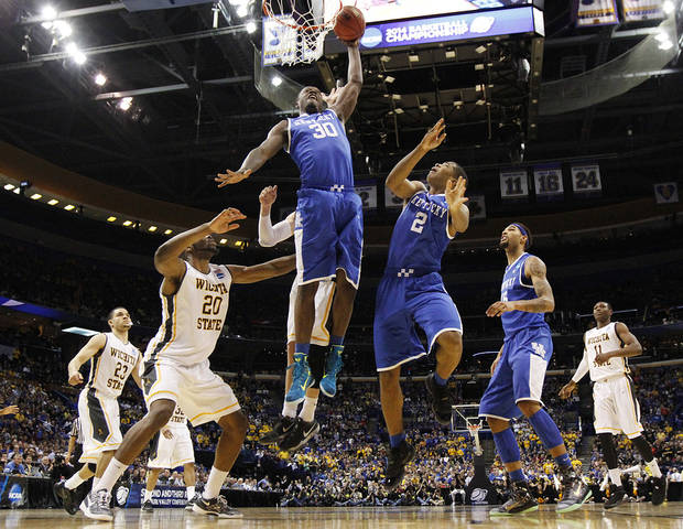 Kentucky forward Julius Randle (30) dunks the ball in second half action during a Third Round NCAA Tournament game between Wichita State and Kentucky on Sunday, March 23, 2014, at the Scottrade Center in St. Louis.  At right is Kentucky guard Aaron Harrison (2).  (AP Photo/ St. Louis Post-Dispatch, Chris Lee)