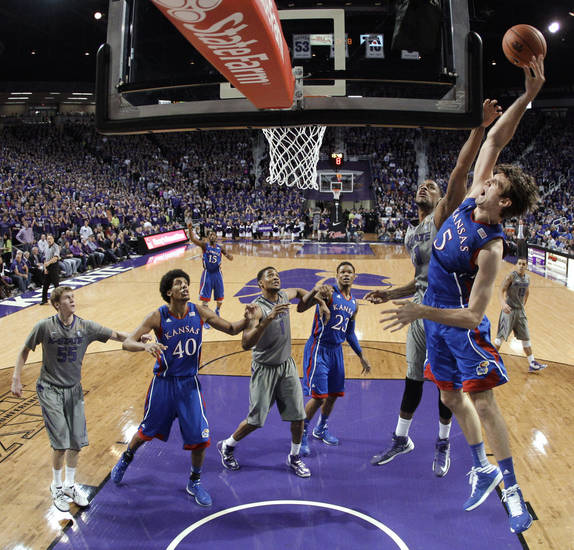 Kansas center Jeff Withey (5) gets past Kansas State guard Shane Southwell to put up a shot during the first half of an NCAA college basketball game Tuesday, Jan. 22, 2013, in Manhattan, Kan. (AP Photo/Charlie Riedel)