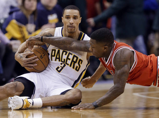 Indiana Pacers guard George Hill, left, keeps the ball away from Chicago Bulls guard Nate Robinson after falling to the floor in the first half of an NBA basketball game in Indianapolis, Monday, Feb. 4, 2013. (AP Photo/Michael Conroy)