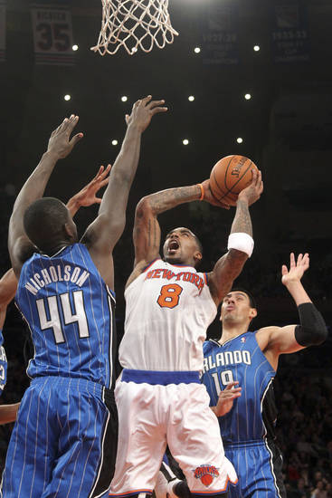 New York Knicks' J.R. Smith goes up against Orlando Magic's Andrew Nicholson (44) and Gustavo Ayon (19) during the first half of an NBA basketball game Wednesday, Jan. 30, 2013, at Madison Square Garden in New York.  (AP Photo/Mary Altaffer)