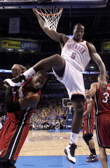 Oklahoma City Thunder's Kendrick Perkins (5) dunks over Miami Heat's Dwyane Wade (3) after a dunk during the NBA basketball game between the Miami Heat and the Oklahoma City Thunder at Chesapeake Energy Arena in Oklahoma City, Sunday, March 25, 2012. Photo by Sarah Phipps The Oklahoman