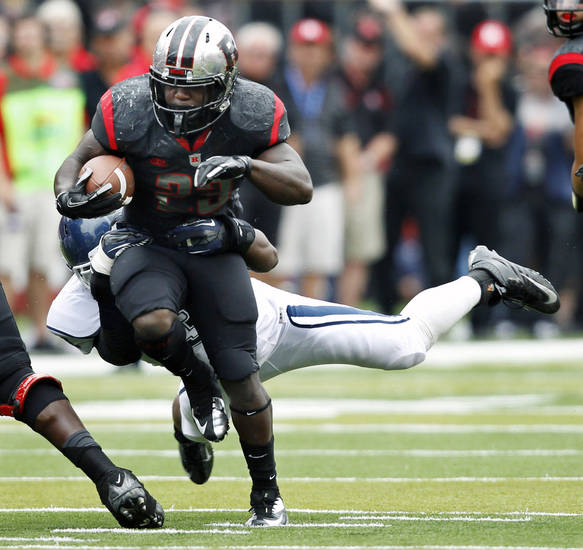 Rutgers running back Jawan Jamison drags a Connecticut defender along as he gains yardage during the second half of an NCAA college football game in Piscataway, N.J., Saturday, Oct. 6, 2012. Rutgers won 19-3. (AP Photo/Mel Evans)