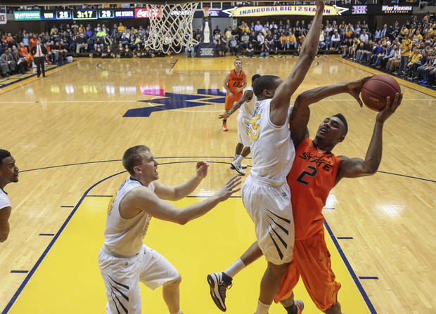 Oklahoma State's Le'Bryan Nash (2) is fouled by West Virginia's Gary Browne (14) during the first half of an NCAA college basketball game in Morgantown, W.Va., on Saturday, Feb. 23, 2013. (AP Photo/David Smith) ORG XMIT: WVDS107