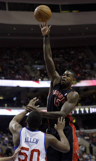 Toronto Raptors' Amir Johnson, top, shoots over Philadelphia 76ers' Lavoy Allen in the first half of an NBA basketball game on Friday, Jan. 18, 2013, in Philadelphia. (AP Photo/Matt Slocum)