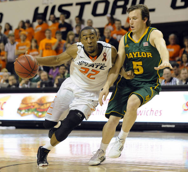 Oklahoma State guard guard Markel Brown, left, drives past Baylor guard Brady Heslip during the second half of an NCAA college basketball game in Stillwater, Okla., Wednesday, Feb. 6, 2013. Brown scored 13 points in the 69-67 win over Baylor. (AP Photo/Brody Schmidt)