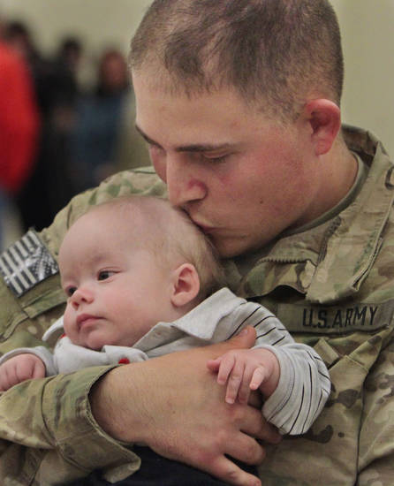 Richard Higgins greets his son Bryson, 4-months, as he and other members of the Oklahoma National Guard return from Afghanistan on Thursday, Jan. 12, 2012, in Norman, Okla.  