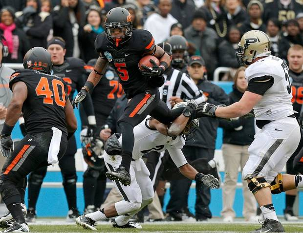 Oklahoma State's Josh Stewart (5) leaps over Purdue's Frankie Williams (2) during the Heart of Dallas Bowl football game between Oklahoma State University and Purdue University at the Cotton Bowl in Dallas, Tuesday, Jan. 1, 2013. Oklahoma State won 58-14. Photo by Bryan Terry, The Oklahoman