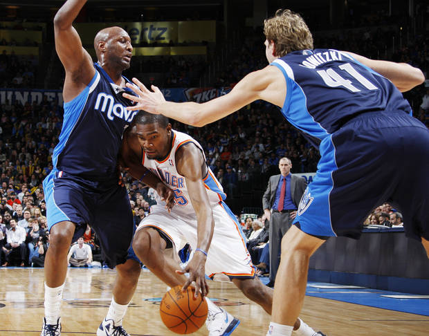 Oklahoma City's Kevin Durant (35) dribbles between Lamar Odom (7) and Dirk Nowitzki (41) of Dallas in the first half of an NBA basketball game between the Oklahoma City Thunder and the Dallas Mavericks at Chesapeake Energy Arena in Oklahoma City, Thursday, Dec. 29, 2011. Photo by Nate Billings, The Oklahoman