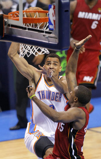 Oklahoma City's Thabo Sefolosha (2) dunks over over Miami's Mario Chalmers (15) during Game 1 of the NBA Finals between the Oklahoma City Thunder and the Miami Heat at Chesapeake Energy Arena in Oklahoma City, Tuesday, June 12, 2012. Photo by Sarah Phipps, The Oklahoman