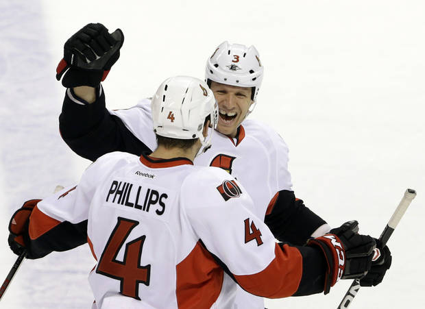 Ottawa Senators defensemen Marc Methot (3) and Chris Phillips (4) celebrate Phillips' goal during the first period of an NHL hockey game against the Florida Panthers, Thursday, Jan. 24, 2013, in Sunrise, Fla. (AP Photo/Wilfredo Lee)