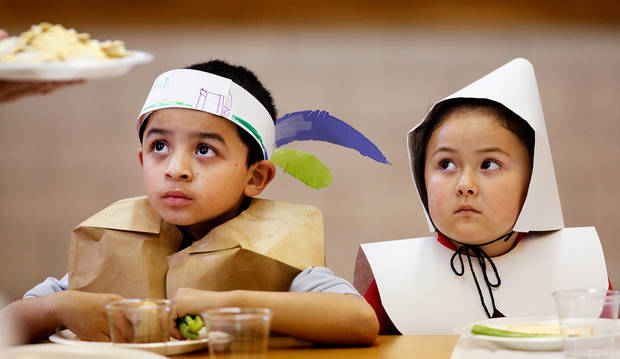 In this photo taken Nov. 22, 2011, Esteban Tapia, left, and classmate Xiomara Fuentes are dressed as an Indian and a Pilgrim as they sit together, waiting for plates of food to be passed around their table during their school's Thanksgiving celebration in Oklahoma City. Kindergarten students at Rancho Village Elementary School dressed as Pilgrims and Indians and feasted on homemade butter they made in their classrooms earlier in the day. They also ate bread, celery and popcorn during the celebration. (AP Photo/The Oklahoman, Jim Beckel)  ORG XMIT: OKOKL103