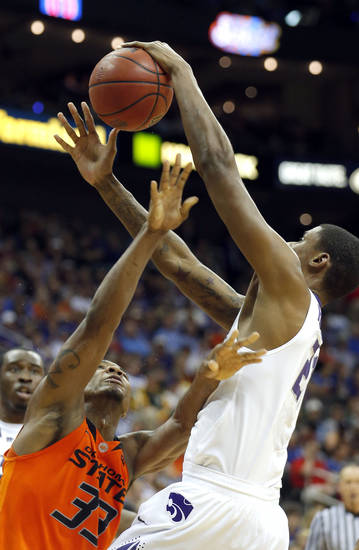 Kansas State's Jordan Henriquez (21) blocks the shot of Oklahoma State's Marcus Smart (33) during the Phillips 66 Big 12 Men's basketball championship tournament game between Oklahoma State University and Kansas State at the Sprint Center in Kansas City, Friday, March 15, 2013. Photo by Sarah Phipps, The Oklahoman