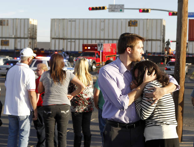   Bystanders react as emergency personnel work the scene where a trailer carrying wounded veterans in a parade was struck by a train in Midland, Texas, Thursday, Nov. 15, 2012. &quot;Show of Support&quot; president and founder Terry Johnson says there are &quot;multiple injuries&quot; after a Union Pacific train slammed into the trailer, killing at least four people and injuring 17 others. (AP Photo/Reporter-Telegram, James Durbin)  