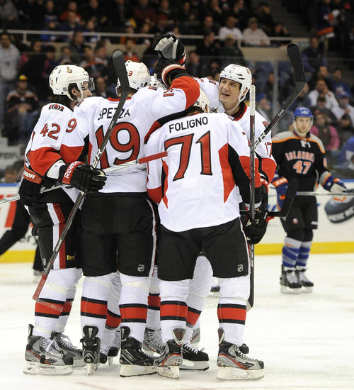 Ottawa Senators' Jim O'Brien (42), Jason Spezza (19), Nick Foligno (71) and Filip Kuba (17) celebrate Spezza's goal against New York Islanders' goalie Kevin Poulin as Islanders' Andrew MacDonald (47) watches from behind in the first period of an NHL hockey game on Monday, Feb. 20, 2012, in Uniondale, N.Y. (AP Photo/Kathy Kmonicek)